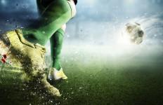 Foot of soccer player kicking ball. Mixed media